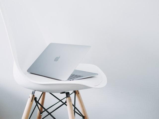 Ilustracja do cytatu Steve'a Jobsa o pragnieniach klientów: srebrny MacBook Air na stylowym białym krześle